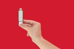 Grüner USB-Blitz an Hand mit lokalisiertem rotem Hintergrund Lizenzfreies Stockfoto
