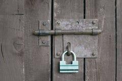 Grüner Verschluss auf einer grauen Holztür Lizenzfreie Stockbilder