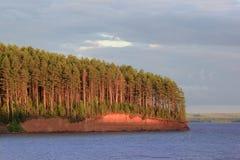 Grüner Wald und der blaue Fluss aalen sich in den Strahlen der untergehenden Sonne Stockfoto