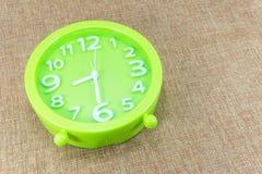 Grüner Wecker auf braune Sackleinenhintergrundshow halber acht O ` Uhr oder 8:30 a M Stockfotografie