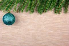 Grüner Weihnachtsball auf einem Textilhintergrund mit Schneetannenbaum Draufsicht, Raum für Ihren Text Lizenzfreies Stockbild