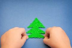 Grüner Weihnachtsbaum im children& x27; s-Hände schnitten vom Plüschmaterial auf der Oberfläche des blauen Papiers Stockfotografie