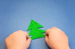 Grüner Weihnachtsbaum im children& x27; s-Hände schnitten vom Plüschmaterial auf der Oberfläche des blauen Papiers Stockfotos