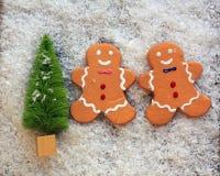 Grüner Weihnachtsbaum im Schnee mit zwei Lebkuchenplätzchen stockbild