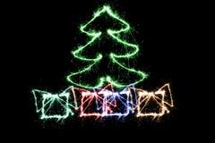 Grüner Weihnachtsbaum und Geschenke gemacht durch Wunderkerze auf einem Schwarzen Stockbild