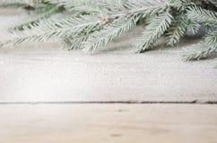 Grüner Weihnachtsbaumast mit Schnee auf einem hölzernen Lizenzfreie Stockfotos