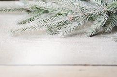 Grüner Weihnachtsbaumast mit Schnee auf einem hölzernen Stockbilder