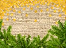 Grüner Weihnachtsbaumast und goldene Sterne auf Leinenstruktur Stockbild