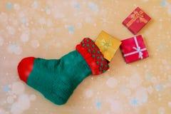 Grüner Weihnachtsstrumpf mit Geschenken Stockfotos
