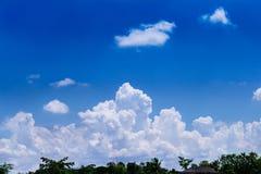 Grüner Wipfel mit Dach des Hauses vorbei auf schönem blauem Himmel und großer Wolkengruppe für Hintergrund lizenzfreie stockfotografie