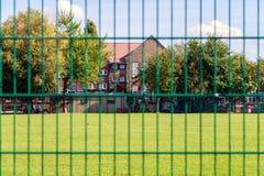 Grüner Zaun und Häuser Stockfotos