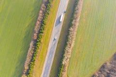 Grünes Ackerland, das Landstraßenvogelperspektive umgibt Landwirtschaftliche Landschaft lizenzfreies stockfoto