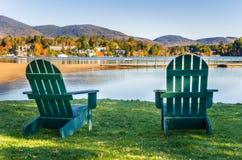 Grünes Adirondack sitzt einer Einfassung ein Mountainsee vor Stockfotografie