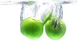Grünes Apfelspritzen über Weiß Lizenzfreies Stockbild