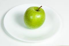 Grünes Apple mit Wasser fällt in eine Platte Stockfoto