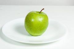 Grünes Apple mit Wasser fällt in eine Platte Stockfotos