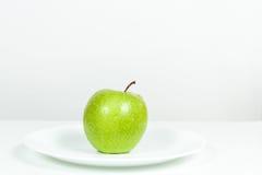 Grünes Apple mit Wasser fällt in eine Platte Stockbild