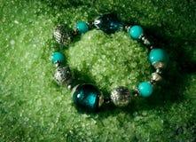 Grünes Armband und Seesalz Stockbild
