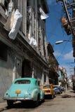 Grünes Auto und Leinen in einer schmalen Straße von Havana Stockfotografie