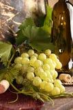 Grünes Bündel der Traube mit Blättern gegen Hintergrundweinflasche Lizenzfreie Stockbilder