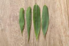 Gr?nes bambou vier Blatt auf h?lzerner Tabelle lizenzfreie stockfotos