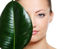 Grünes Blatt, das eine Hälfte des schönen Frauengesichtes schattiert Lizenzfreies Stockfoto