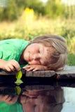 Grünes Blattschiff in der Kinderhand im Wasser, Junge im Parkspiel mit Lizenzfreie Stockbilder