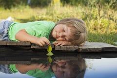 Grünes Blattschiff in der Kinderhand im Wasser, Junge im Parkspiel mit Boot im Fluss stockfotografie