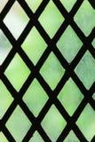 Grünes Buntglasfenster mit regelmäßigem Blockmuster Stockfotografie