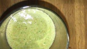 Grünes Cocktail, das in ein Glas auf einem Holztisch gießt stock footage