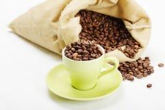 Grünes Cup mit Kaffeebohnen Stockfotos