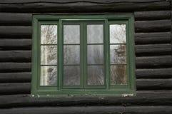 Grünes das gemaltes Fenster und raue Schwarze meldet ein altes Blockhaus-BU an Lizenzfreie Stockfotos