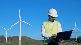 Grünes Energiekonzept Ein Mann betrachtet Windkraftanlagen und Arten auf seinem Laptop 4K stock footage