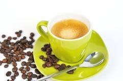 Grünes Espressocup mit Kaffeebohnen und Löffel Stockfotografie