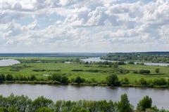 Grünes Feld auf der Flussbank Lizenzfreie Stockbilder