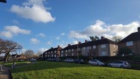 Grünes Feld, Häuser und blauer Himmel Stockfotografie
