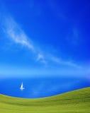 Grünes Feld, Meer und Himmel Stockbild
