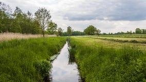 Grünes Feld mit Fluss im mittleren und bewölkten Himmel Lizenzfreies Stockfoto