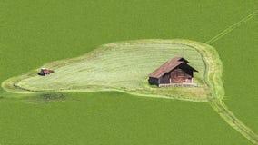 Grünes Feld mit Haus und Mäher Stockbilder