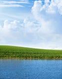 Grünes Feld mit See Stockfotos