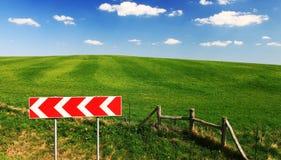 Grünes Feld mit Wolken, blauem Himmel und Verkehrsschild Stockfotografie