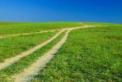 Grünes Feld, Straßen und Sonnehimmel Lizenzfreie Stockfotografie
