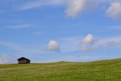 Grünes Feld und blauer Himmel mit Haus Stockfoto
