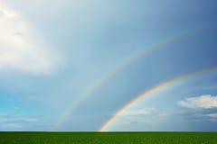 Grünes Feld und doppelter Regenbogen Stockfotos