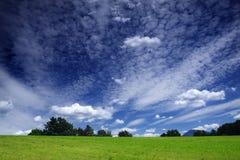 Grünes Feld und drastischer Himmel Lizenzfreies Stockfoto