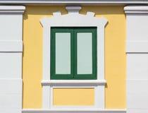Grünes Fenster auf gelber Wand von der Außenseite Lizenzfreie Stockbilder