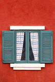 Grünes Fenster auf roter Wand stockfotografie