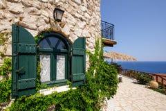 Grünes Fenster der Weinlese auf einem Backsteinhaus mit Ozeanhintergrund, Griechenland Stockfotografie