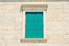 Grünes Fenster gegen eine alte Wand Lizenzfreie Stockbilder