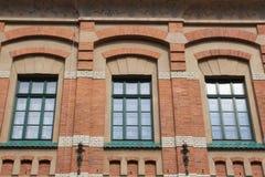 Grünes Fenster mit drei Designen auf der Fassade eines Backsteinhauses Stockfotografie